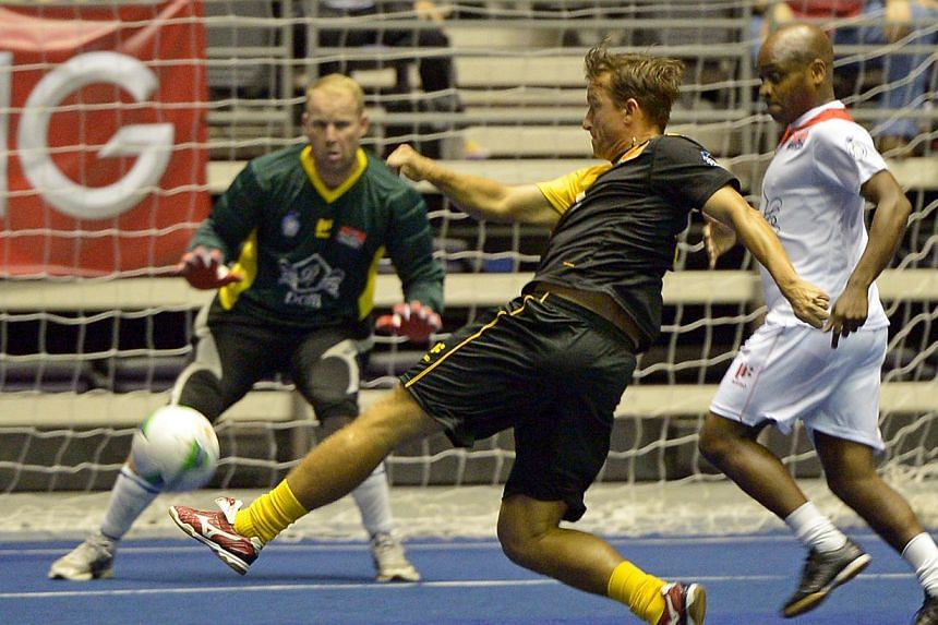 Manchester United goalkeeper Nick Culkin (left) faces a shot from Liverpool's Vladimir Smicer (centre) while Paul Parker watches on at the IG Masters Sixes at the Singapore Indoor Stadium on Sunday, Oct 20, 2013. -- ST PHOTO:DESMOND WEE