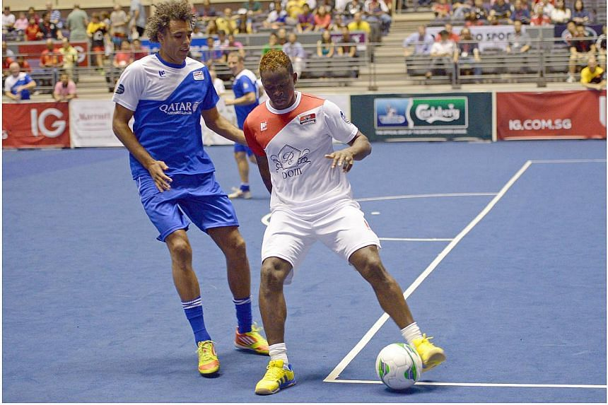 EPL All Stars' Pierre van Hooijdonk (left) tries to stop Manchester United's Louis Saha at the IG Masters Sixes at the Singapore Indoor Stadium on Sunday, Oct 20, 2013. -- ST PHOTO: DESMOND WEE