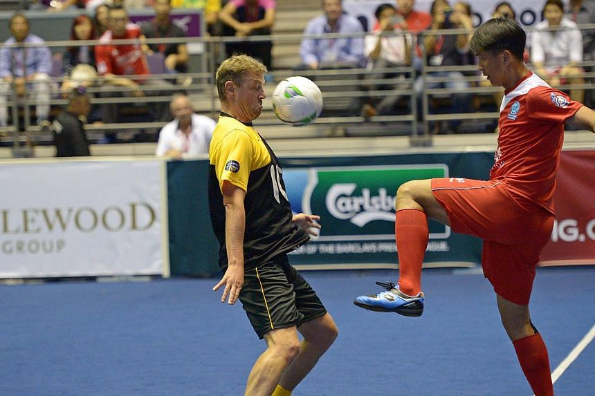 Singapore's Lim Tong Hai (right) attempts to stop Liverpool's Stephane Henchoz at the IG Masters Sixes at the Singapore Indoor Stadium on Sunday, Oct 20, 2013. -- ST PHOTO: DESMOND WEE