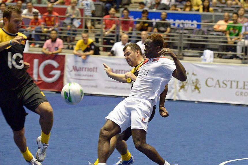 Liverpool's Patrik Berger (left) and Steve Harkness attempt to stop Manchester United striker Louis Saha (in white) at the IG Masters Sixes at the Singapore Indoor Stadium on Sunday, Oct 20, 2013. -- ST PHOTO: DESMOND WEE