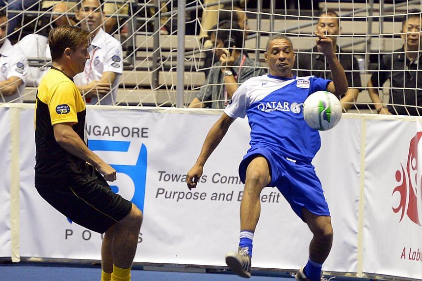Liverpool's Vladimir Smicer (left) and EPL All Stars' Des Walker compete for the ball at the IG Masters Sixes at the Singapore Indoor Stadium on Sunday, Oct 20, 2013. -- ST PHOTO: DESMOND WEE