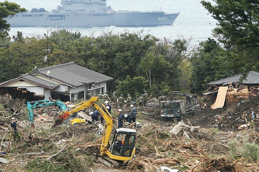 Soldiers remove debris from damaged houses after a landslide at Oshima island, 120km south of Tokyo on Saturday, Oct 19, 2013.Hundreds fled their homes on Sunday, Oct 20, 2013, on a Japanese island already devastated by a typhoon for fear that