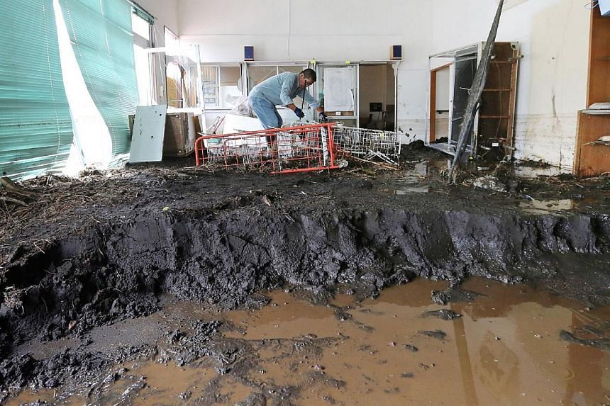 A man scoops out the mud accumulated in his house after a landslidecaused by heavy rains from Typhoon Wipha buried houses at Oshima island, 120km south of Tokyo on Saturday, Oct 19, 2013. -- PHOTO: AFP