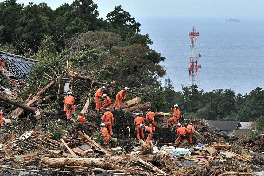 Policemen search for missing people after a landslide on Oshima island, 120km south of Tokyo on Friday, Oct 18, 2013. -- PHOTO: AFP