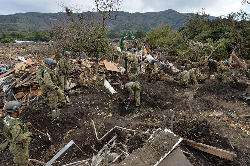 Ground Self-Defence Force troops search for missing people after a landslide on Oshima island, 120km south of Tokyo on Friday, Oct 18, 2013. -- PHOTO: AFP