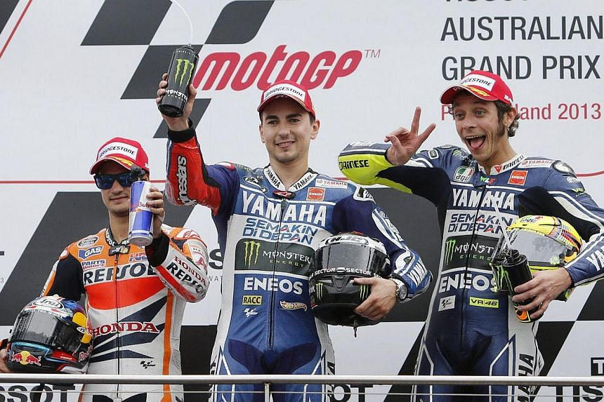 Yamaha MotoGP rider Jorge Lorenzo (centre), who finished first, poses for photographers with teammate Valentino Rossi (right) and Honda's Dani Pedrosa as they celebrate on the podium after the Australian Grand Prix at Phillip Island circuit on Sunday