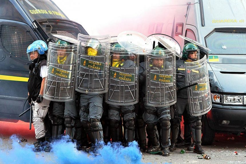 Members of the Guardia di Finanza protect themselves as they stand in front of the Economy minister during an anti-austerity protest on Oct 19, 2013 in Rome. -- PHOTO: AFP