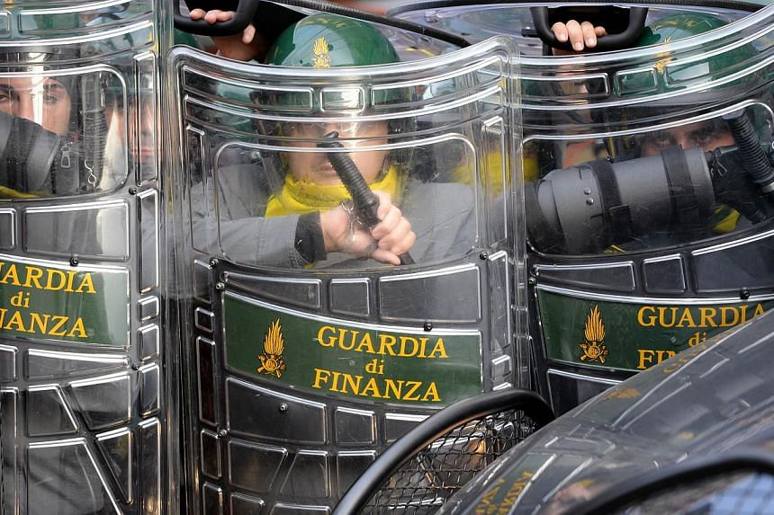 Members of the Guardia di Finanza protect themselves during clashes on the sidelines of an anti-austerity protest on Oct 19, 2013 in Rome. -- PHOTO: AFP