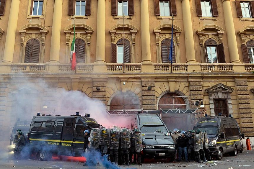 Members of the Guardia di Finanza protect themselves as they stand in front of the Economy minister during clashes on the sidelines of an anti-austerity protest on Oct 19, 2013 in Rome. -- PHOTO: AFP