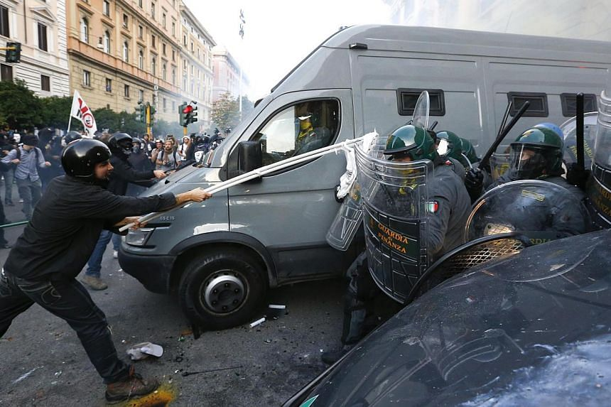 A protester clashes with Guardia di Finanza as they respond to a protest in front of the Ministry of Finance building in downtown Rome, Oct 19, 2013. -- PHOTO: REUTERS