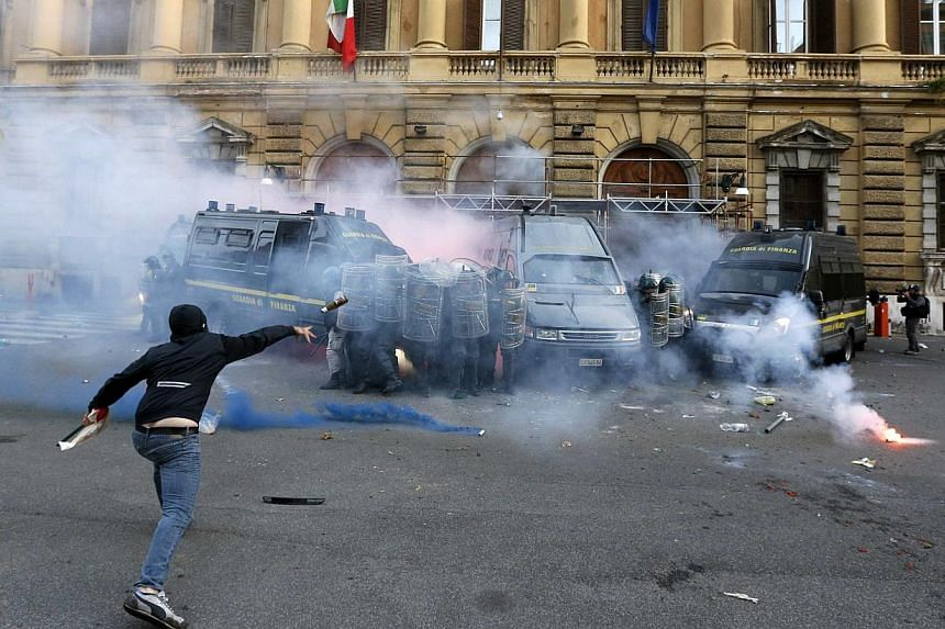 A demonstrator throws a bottle at Guardia di Finanza during a protest in downtown Rome, Oct 19, 2013. Tens of thousands of people took to the streets in Italy and Portugal for mostly peaceful protests against austerity on Saturday, but there were cla