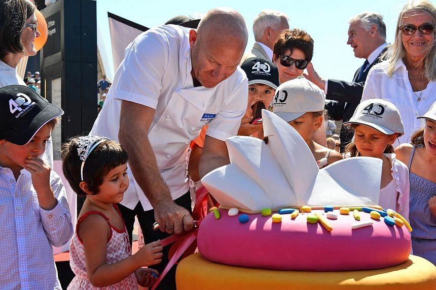 Celebrity chief Matt Moran (centre) cuts pieces of a giant cake of the Sydney Opera House as the world heritage-listed building celebrates its 40th birthday on Oct 20, 2013. -- PHOTO: AFP