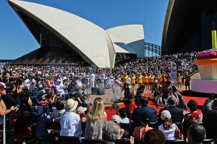 Aboriginal dancers (centre, right) perform a smoking ceremony on the steps of the Sydney Opera House as the world heritage-listed building celebrates its 40th birthday on Oct 20, 2013. -- PHOTO: AFP