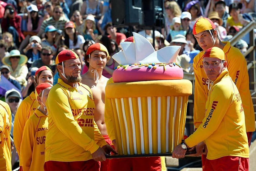 Australian surf lifesavers carry a giant cake (centre) of the Sydney Opera House as the world heritage-listed building celebrates its 40th birthday on Oct 20, 2013. -- PHOTO: AFP