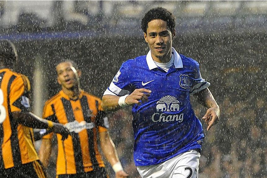 Everton's Steven Pienaar celebrates in the rain after scoring his side's second goal against Hull City during their Barclays Premier League match at Goodison Park, Liverpool, Saturday Oct 19, 2013. -- PHOTO: AP