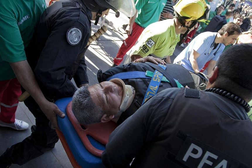 Police and paramedics carry a wounded passenger to an ambulance after a commuter train slammed into the end of the line when arriving to Once Central station in Buenos Aires, Argentina, early Saturday, Oct 19, 2013. -- PHOTO: AP