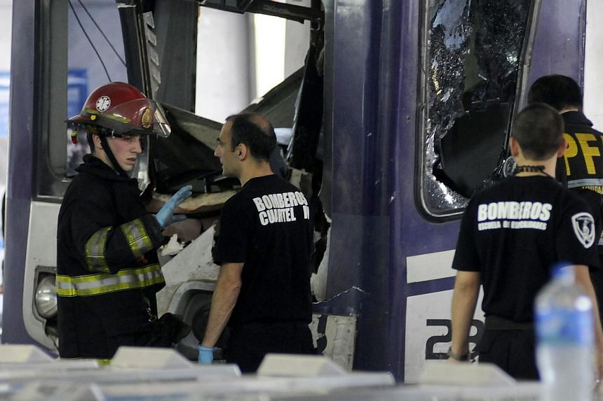 Picture released by NA showing firefighters inspecting the commuter train that apparently failed to stop and crashed at the end of the line at the Once railway terminal in Buenos Aires, on Oct 19, 2013. -- PHOTO: AFP