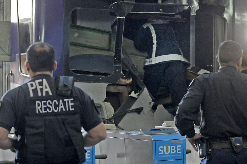 Picture released by NA showing a firefighter inspecting the commuter train that apparently failed to stop and crashed at the end of the line at the Once railway terminal in Buenos Aires, on Oct 19, 2013. -- PHOTO: AFP