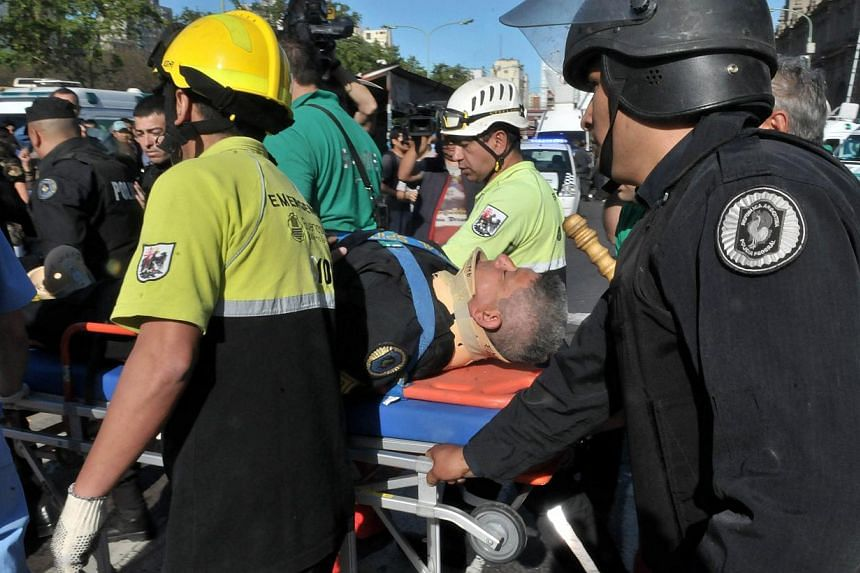 An injured man is evacuated after a commuter train that apparently failed to stop and crashed at the end of the line at the Once railway terminal in Buenos Aires, on Oct 19, 2013. -- PHOTO: AFP