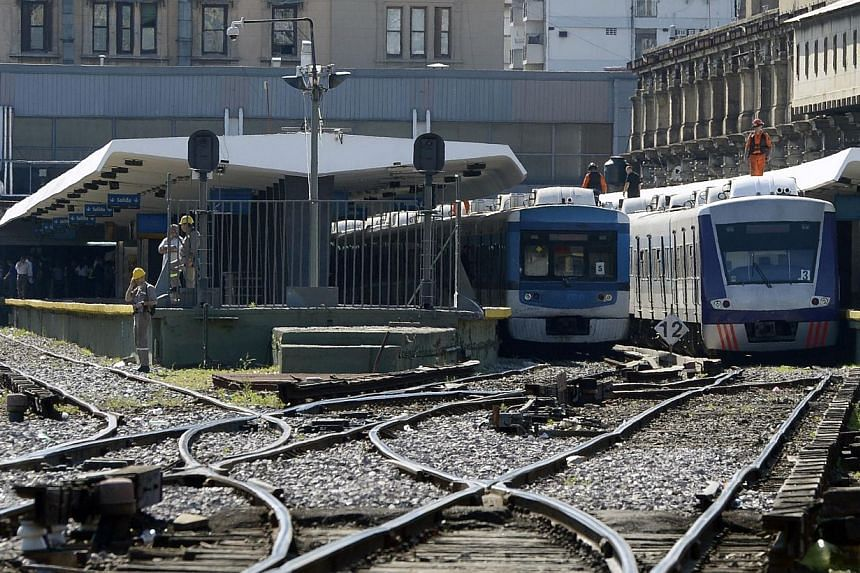 Rescue workers (in orange suit) are seen at the Once railway terminal in Buenos Aires after a commuter train (second right) apparently failed to stop and crashed at the end of the line, on Oct 19, 2013. -- PHOTO: AFP