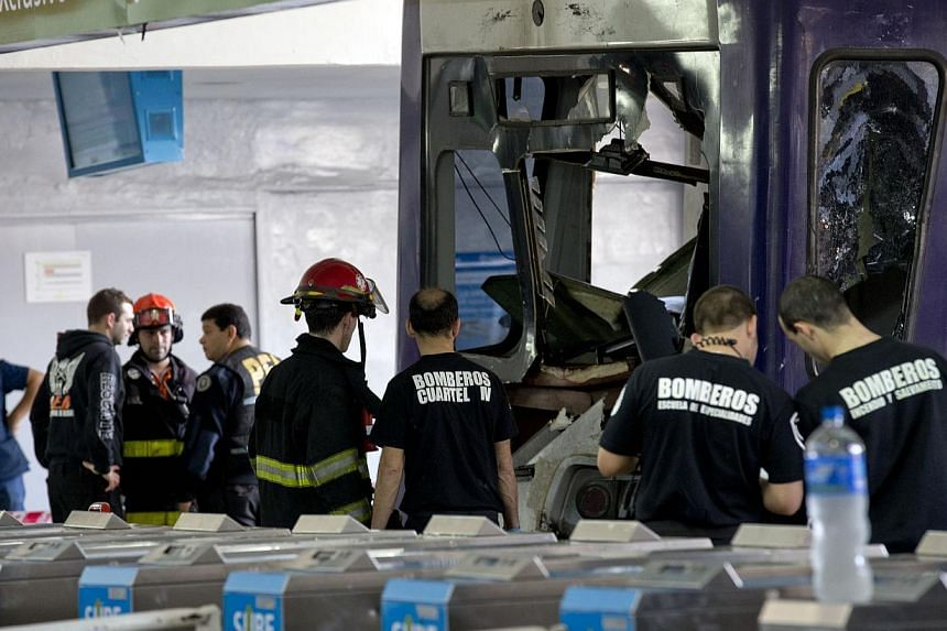 Police and firemen work on a commuter train that slammed into the end of the line when arriving to Once central station in Buenos Aires, Argentina, Saturday, Oct 19, 2013. -- PHOTO: AP