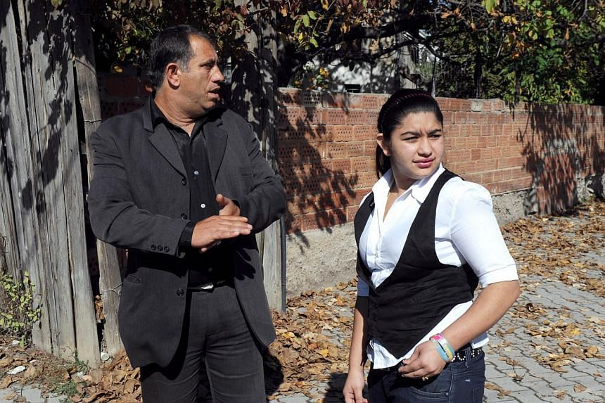 Leonarda Dibrani, the 15 year-old Roma schoolgirl whose deportation from France sparked a huge outcry, stands with her father Resat Dibrani at their temporary home town in Mitrovica on October 19, 2013.Unidentified assailants on Sunday attacked