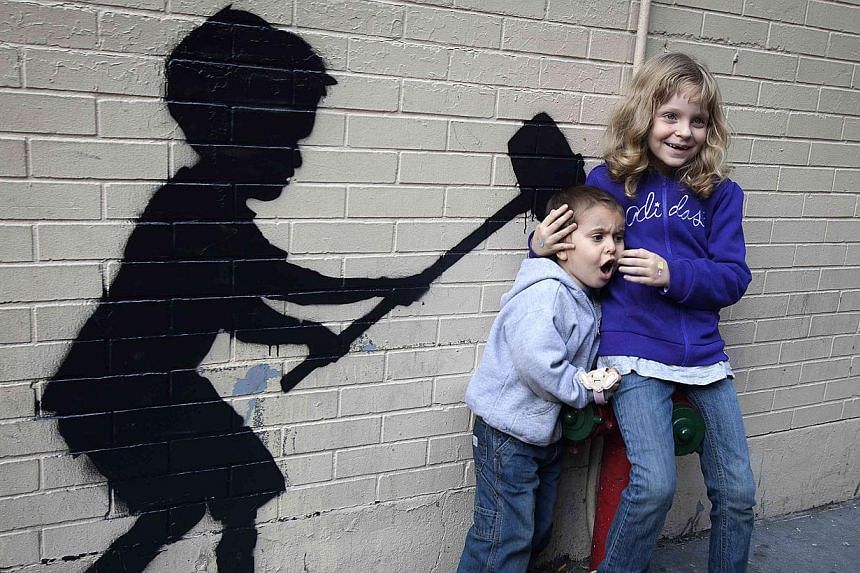 Children pose for their parents with a new installation of British graffiti artist Banksy's art, in New York on Sunday, Oct 20, 2013. -- PHOTO: REUTERS