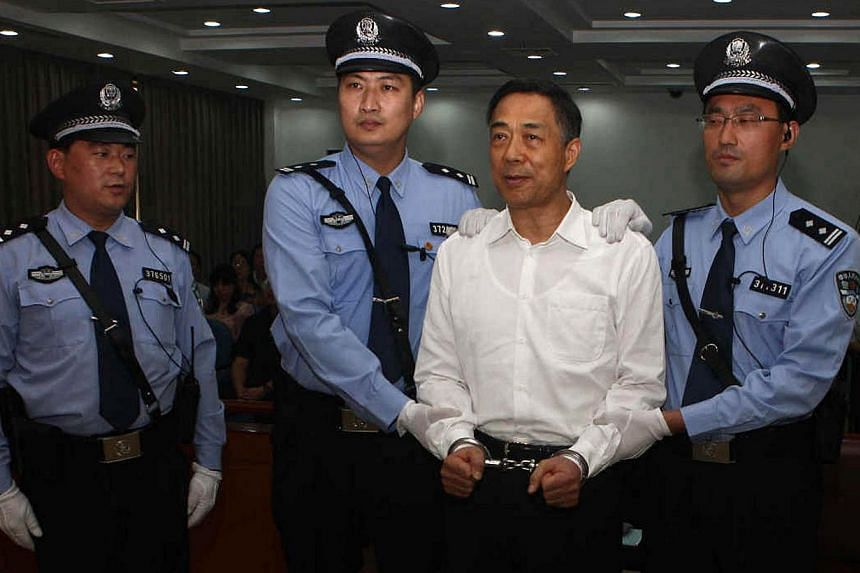 This picture taken on Sept 22, 2013, and released by Jinan Intermediate People's Court shows Chinese political star Bo Xilai (second from right) wearing a pair of handcuffs as he stands in a courtroom in Jinan, east China's Shandong province. A