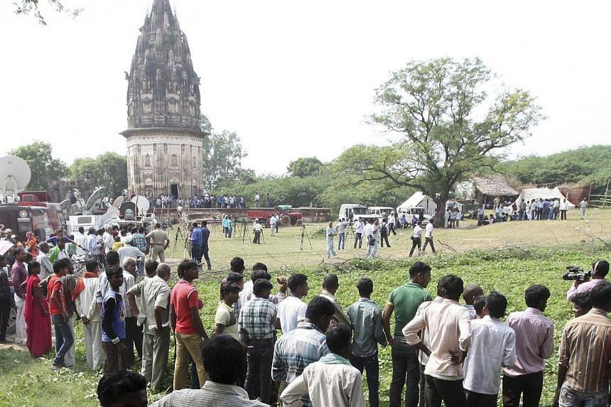 Onlookers stand at the site where the state archaeological survey of India has sent a team of archaeologists to start digging at Daundia Khera village in the northern state of Uttar Pradesh on Oct 18, 2013. Indian archaeologists said on Monday,
