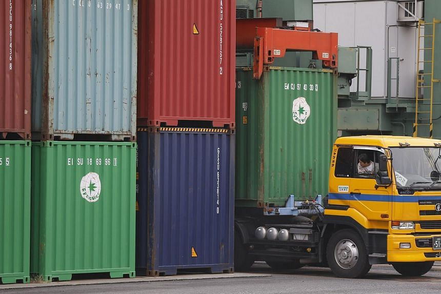 A container is loaded onto a truck at a pier in Tokyo on Monday, Oct 21, 2013. Japan's export growth fell well short of expectations in September, data showed on Monday, suggesting the weaker yen resulting from the government's Abenomics stimulus pol