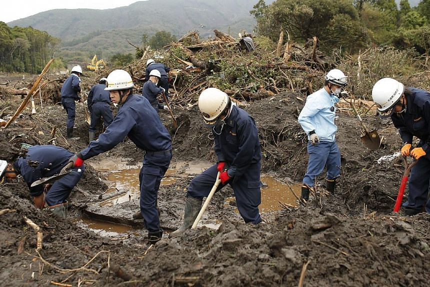 Fire brigade members continue the search for missing people on Monday, Oct 21, 2013, after a landslide caused by heavy rains from Typhoon Wipha hit Oshima island, south of Tokyo. The search resumed on Monday for 18 people still missing after las
