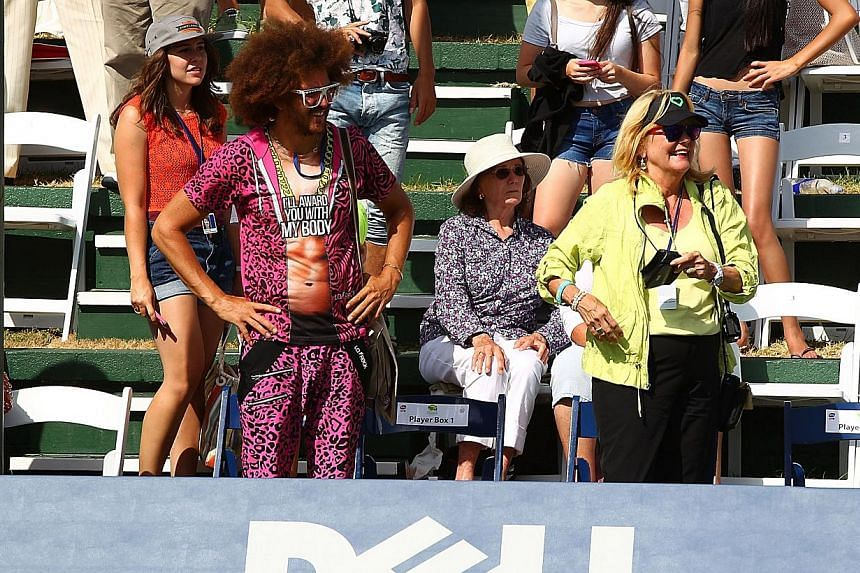 Redfoo (second from left) of LMFAO watches Victoria Azarenka of Belarus play at the Southern California Open on Day Six at La Costa Resort & Spa on Aug 3, 2013 in Carlsbad, California. Azarenka says that watching her boyfriend Redfoo, the si