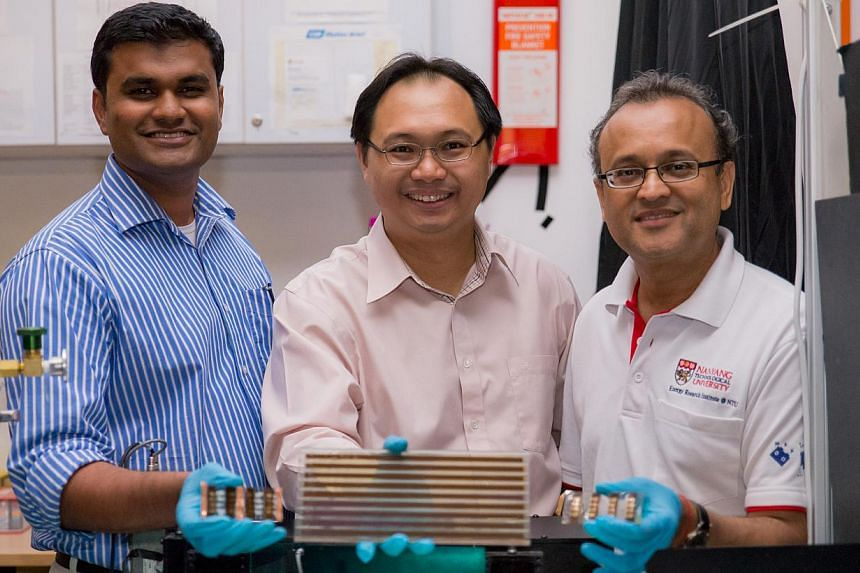 Prof Subodh Mhaisalkar (left) and Dr Nripan Mathews (right) hold the new Perosvkite solar cells made in NTU labs with hopes of using it to develop a solar cell module, as held by Prof Sum Tze Chien. Scientists from Nanyang Technological Universi