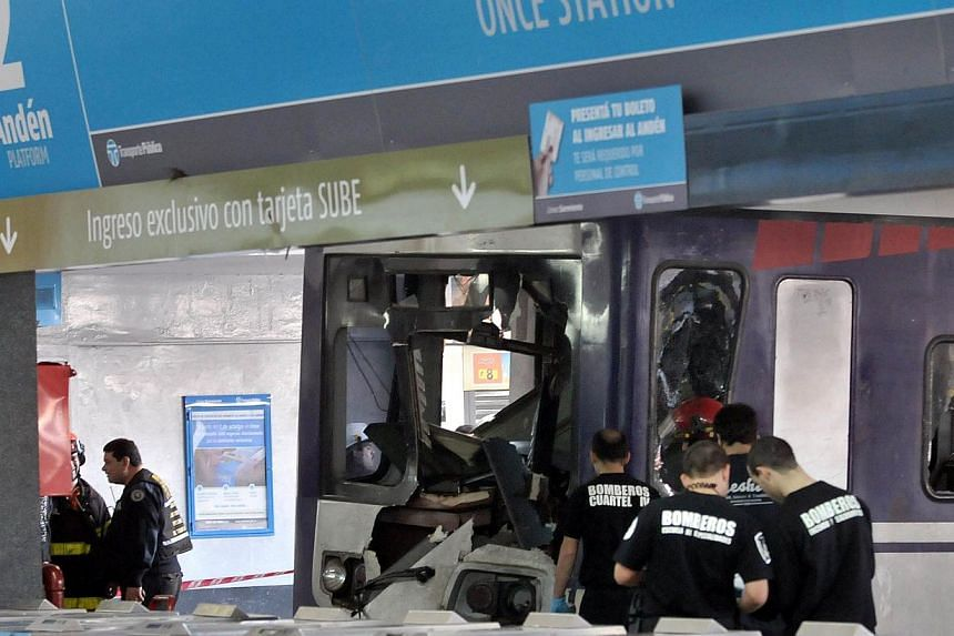 Firefighters inspect a commuter train that apparently failed to stop and crashed at the end of the line at the Once railway terminal in Buenos Aires, on Oct 19, 2013. -- PHOTO: AFP