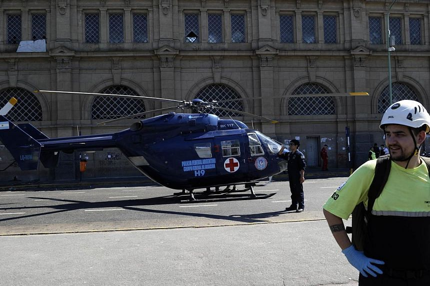 A police helicopter for emergency medical services is seen outside the Once railway terminal in Buenos Aires after a commuter train apparently failed to stop and crashed at the end of the line, on Oct 19, 2013. -- PHOTO: AFP