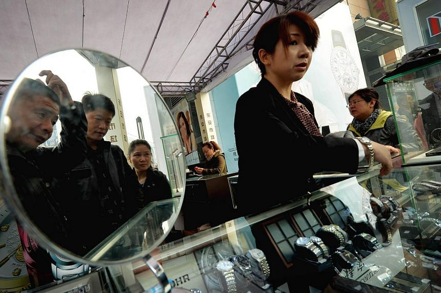 Chinese shoppers look at watches for sale on the Wangfujing shopping street in Beijing on Oct 18, 2013. China's Cabinet called for greater effort in revamping the economy because a recovery is not yet solid, seeking quicker progress on restructuring