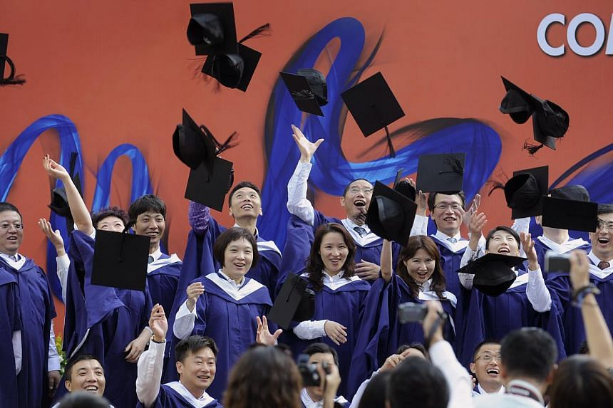 Graduates from the APEX MBA programme at the NUS Business School posing for photos at the commencement ceremony on July 6, 2011. The NUS Business School's double-degree programme with the University of California, Los Angeles (UCLA) has retained its
