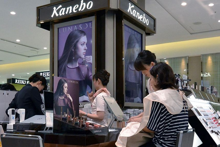 Japanese cosmetics company Kanebo employees attend to a customer in Tokyo on Sept 14, 2013. More than 15,000 people in Japan have been left with skin blotches caused by a chemical contained in popular skin-whitening creams, the maker of the products