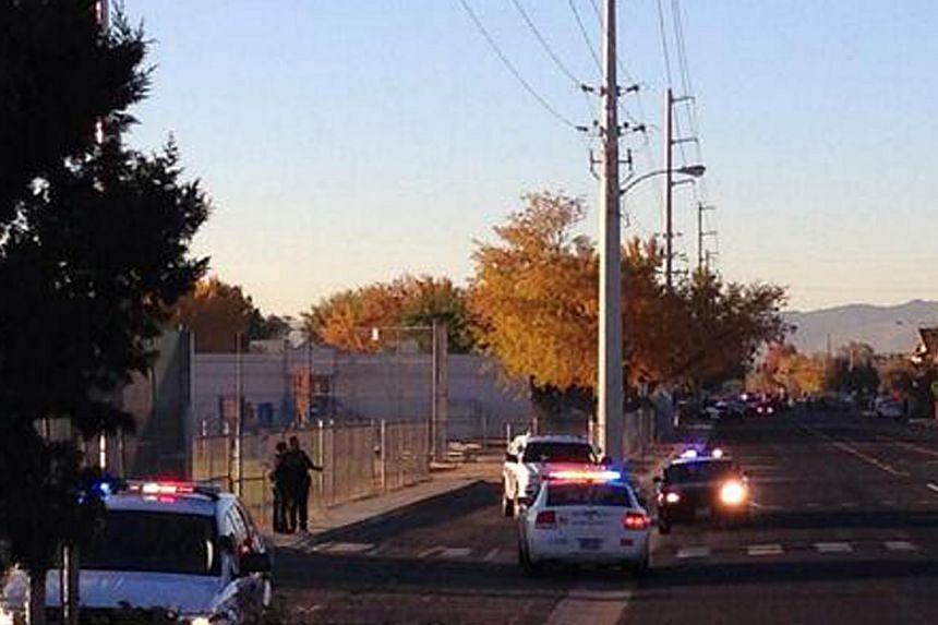 In this photo provided by Jerry Davis, police gather near Sparks Middle School after a shooting at the school, on Monday, Oct. 21, 2013, in Reno, Nev. A teenager opened fire at a school in the United States (US) state of Nevada on Monday, killing a t