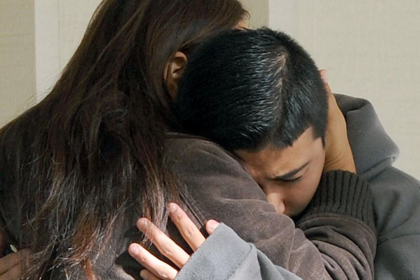 Jorge Martinez, 13, right, cries in his mother Norma's arms following the shooting that left two dead, including the shooter, at Sparks Middle School on Monday, Oct. 21, 2013. A teenager opened fire at a school in the United States (US) state of Neva