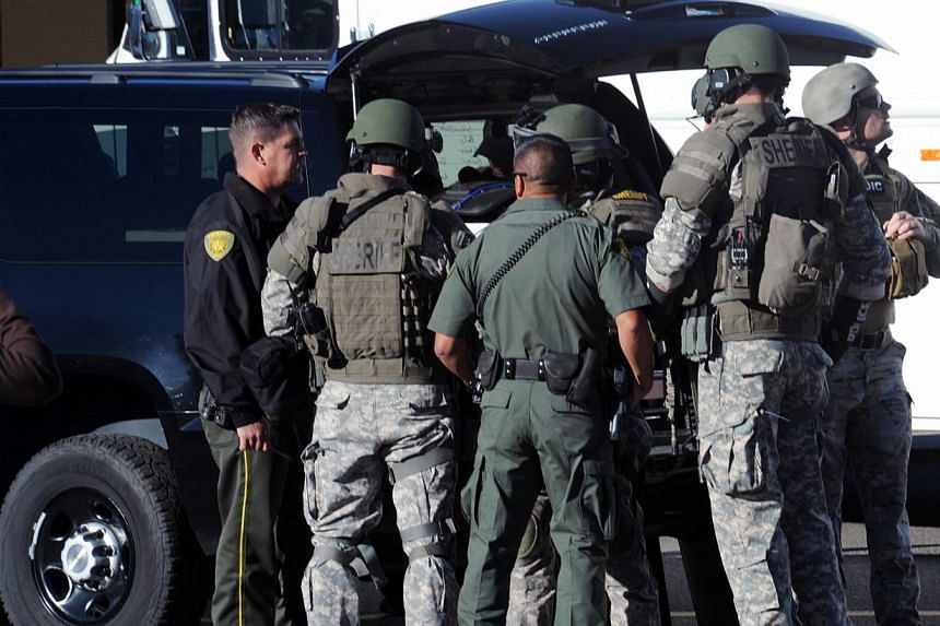 Law enforcement personnel gather at the scene of a shooting at Sparks Middle School in Sparks, Nevada on Monday, Oct 21, 2013. A teenager opened fire at a school in the United States (US) state of Nevada on Monday, killing a teacher and critically wo