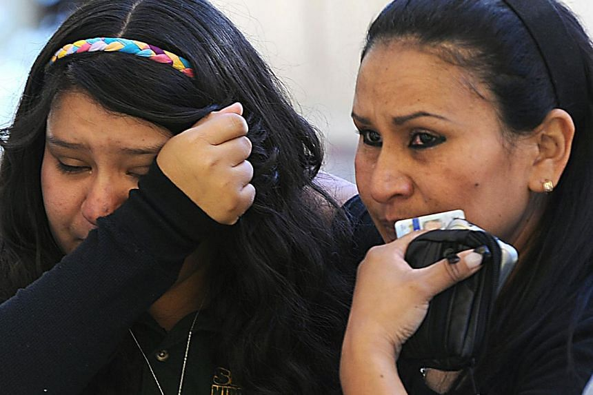 A tearful Michelle Hernandez, left, is led away from Agnes Risley Elementary School following a shooting at Sparks Middle School in Sparks, Nevada on Monday, Oct 21, 2013. A teenager opened fire at a school in the United States (US) state of Nevada o