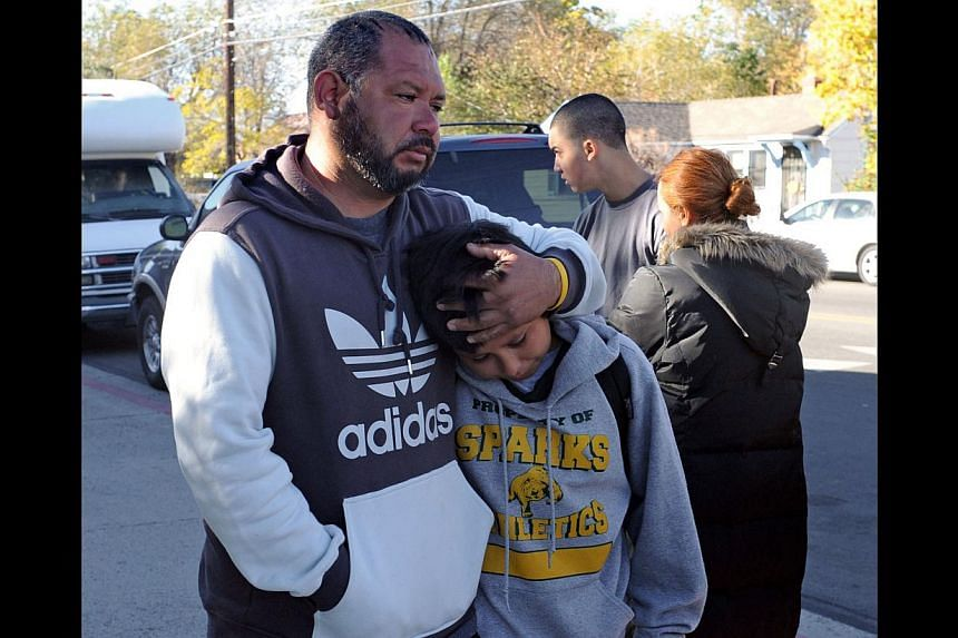 A unidentified parent holds his son, who was crying, at Sparks high school where some student were taken after a shooting that left two dead at Sparks Middle School on Oct 21, 2013, in Sparks, Nevada. A teenager opened fire at a school in the United