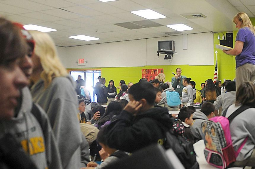 Students from Sparks Middle School huddle together in the school's cafeteria after the school shooting in Sparks, Nevada, on Oct 21, 2013. A teenager opened fire at a school in the United States (US) state of Nevada on Monday, killing a teacher and c