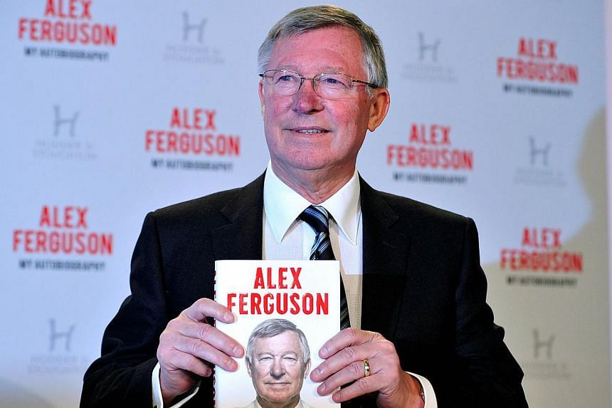 Former Manchester United manager Alex Ferguson poses with a copy of his autobiography titled My Autobiography during a press conference to mark the launch of the book in central London on Tuesday, Oct 22, 2013.Ferguson launched his new autobiog