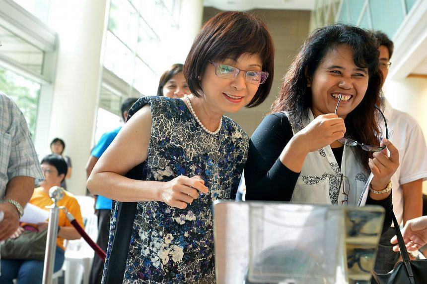 Dr Amy Khor (centre) tries on a pair of glasses at the frame-selection section of the eyecare screening station, one of the free health screening services provided at Jurong Medical Centre on Tuesday, Oct 22, 2013.Close to 250 needy people had