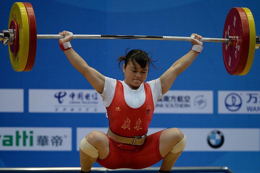 Li Yajun of Guangdong Province lifts to break a world record of 105kg and winning gold in the Women's 53kg weightlifting group during the 12th National China Games in Shenyang, Liaoning Province on Sept 3, 2013. Li gave China their second gold a