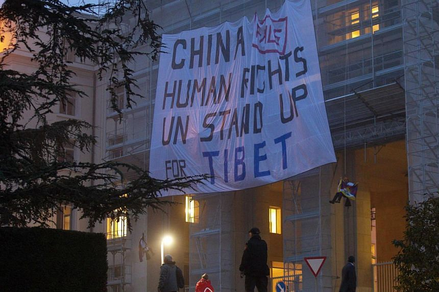 Members of the Students for a Free Tibet organisation display a banner on scaffolding in front of the European headquarters of the United Nations in Geneva on Tuesday, Oct 22, 2013.Tibetan activists protesting at China's rule over Tibet scaled
