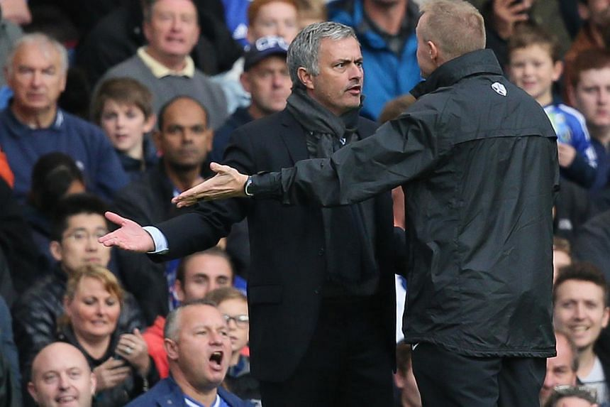Chelsea's manager Jose Mourinho, left, gestures and looks at the fourth official Trevor Kettle, right, he was then sent off by referee Anthony Taylor during the English Premier League soccer match between Chelsea and Cardiff City at Chelsea's Stamfor