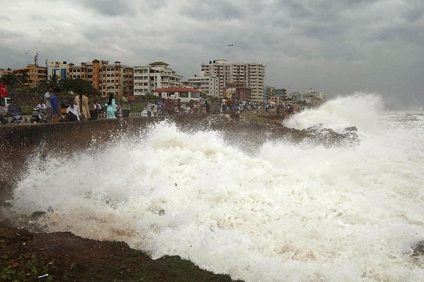 People watch high tide waves as they stand at the Bay of Bengal coast in Vishakhapatnam, India, on Saturday, Oct 12, 2013. The likes of Cyclone Phailin or Typhoon Wipha are unlikely to ever hit Singapore, experts claim. -- FILE PHOTO: AP